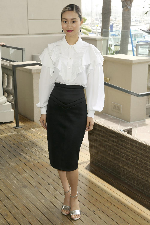 Botas altas negras, falda negra, con camisa blanca y saco de